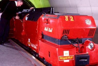 Man working on red Royal Mail postal train