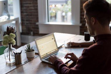 man works on laptop on wooden desk