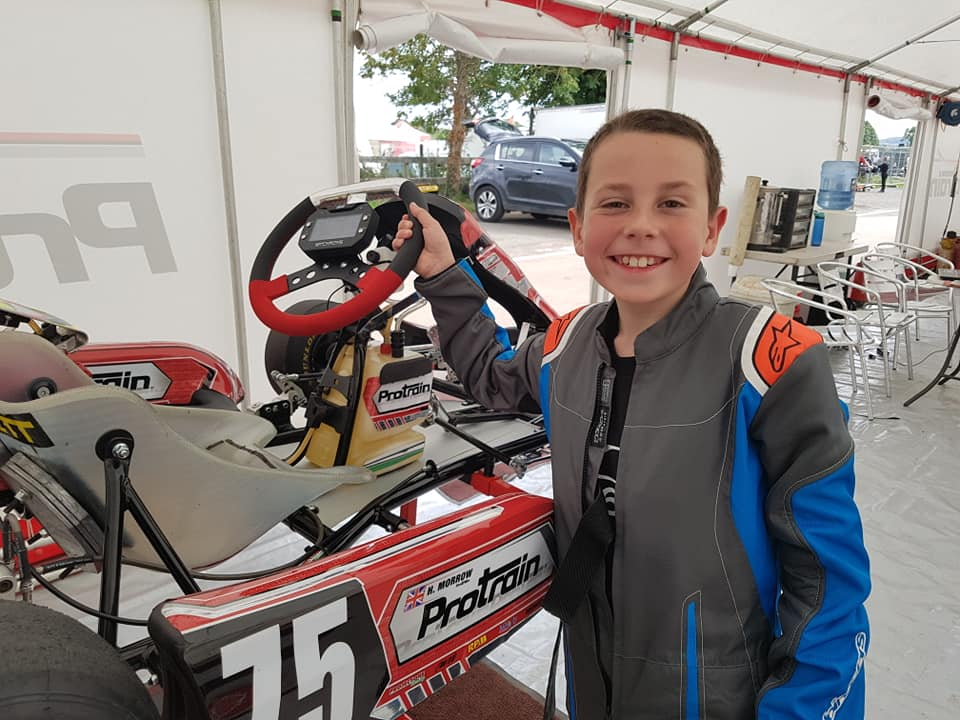 Harrison posing in a tent with his Kart
